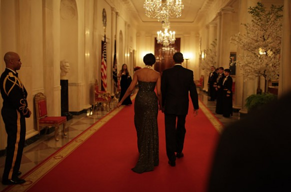 obama with michelle walking down a whitehouse corridor