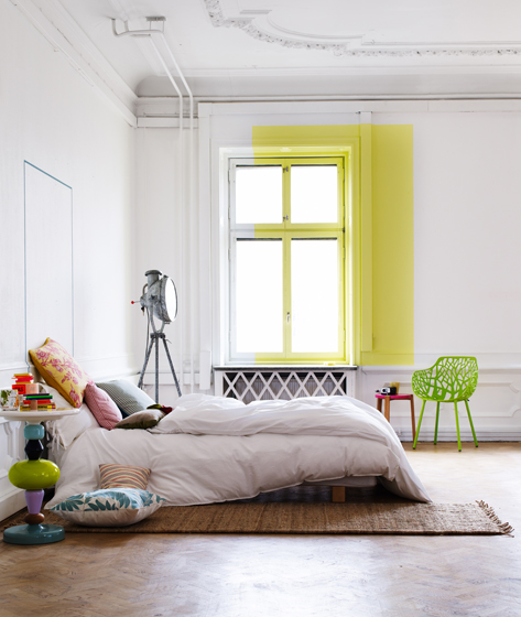 A splash of yellow on the wall is the focus here but also balances the other smaller colorful accent pieces on the floor
