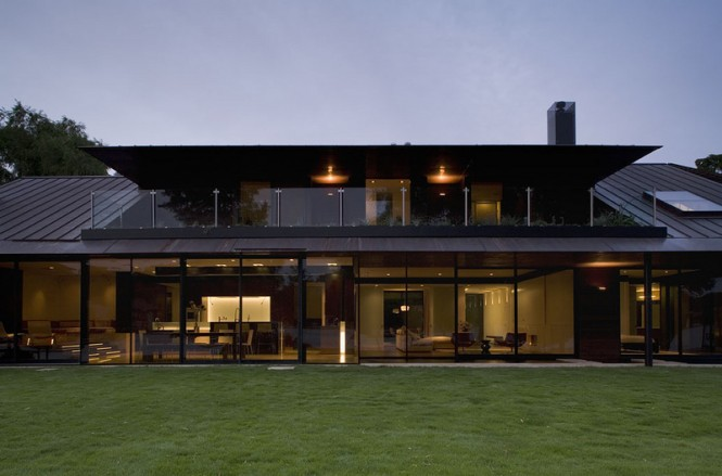 Glass paneled walls surround the entire house. A glass balcony was installed into the roof. The traditional gabers and gable roof were transformed to look more abstract.