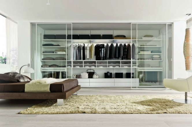 This particular closet space is installed inside the wall and includes glass door panels that slide into the sides of the wall, which expands bedroom space. The different size shelves and compartments are versatile for various types of wardrobe.