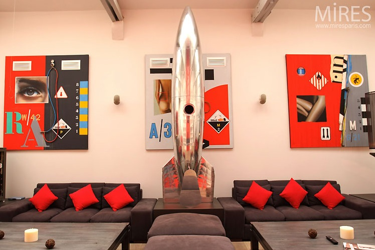 metal spaceship sculpture and red and black wall art in paris loft