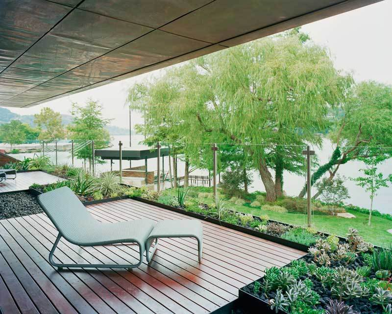 A modern balcony, surrounded by green plants, is even more exposed to the natural world right in front of the house with the use of glass panels.