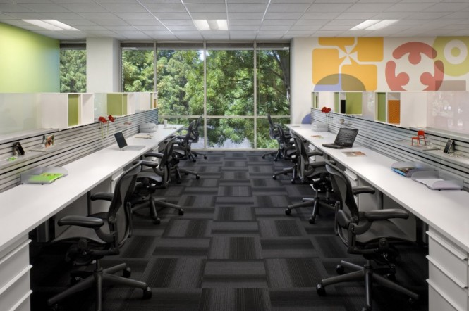 These desks are bench-like and shared, but for those engaged in sensitive work such as human resources,  more private semi-enclosed offices were designed, using white noise technology to maintain acoustic privacy.