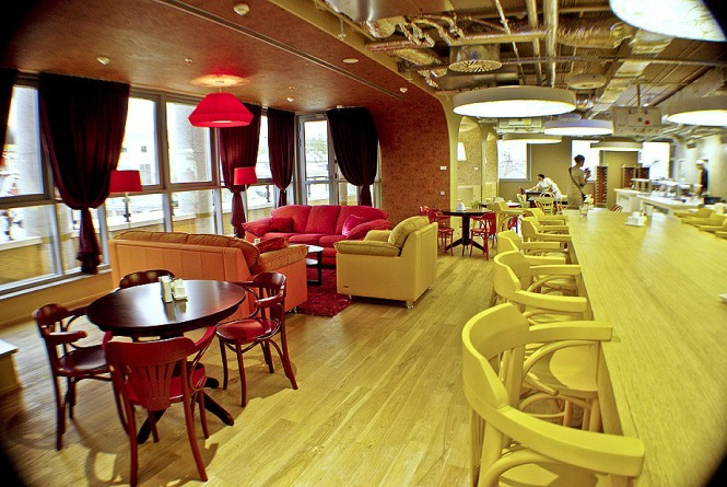 A European style coffee bar is a nice accent to the tables and chairs and lounging areas of the office cafeteria.