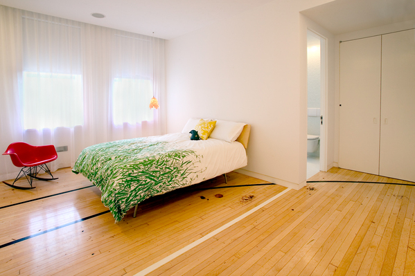 """The Apartment"" group wanted to retain some of elements of the old basketball court, and so decided to keep the basketball court flooring in the private areas of the house, such as this bedroom."