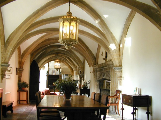The arched ceilings of this hallway are stunning, and reminiscent of a quintessential castle dining hall. Stone is omnipresent here, appearing in the arches of the ceiling, in the large fireplace, and on the floor. The fireplace is intricately and ornately carved. The wooden furniture is sparse but also quintessential of castle decor. Like in most castle halls,  a rich brown, wooden  bench, chairs, and smaller sidetable decorate the hall. The large lantern hanging above the dining table is the main source of light and the wooden doors curve upwards to form a pointed arch as well. It is easy to be transported to a different era when looking at this room. Photo Credit