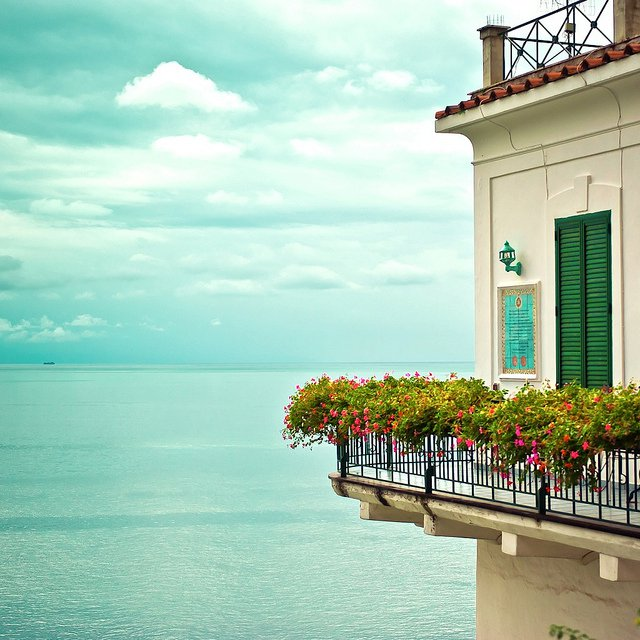 Can you imagine standing on this balcony that practically hangs over clear blue waters? via
