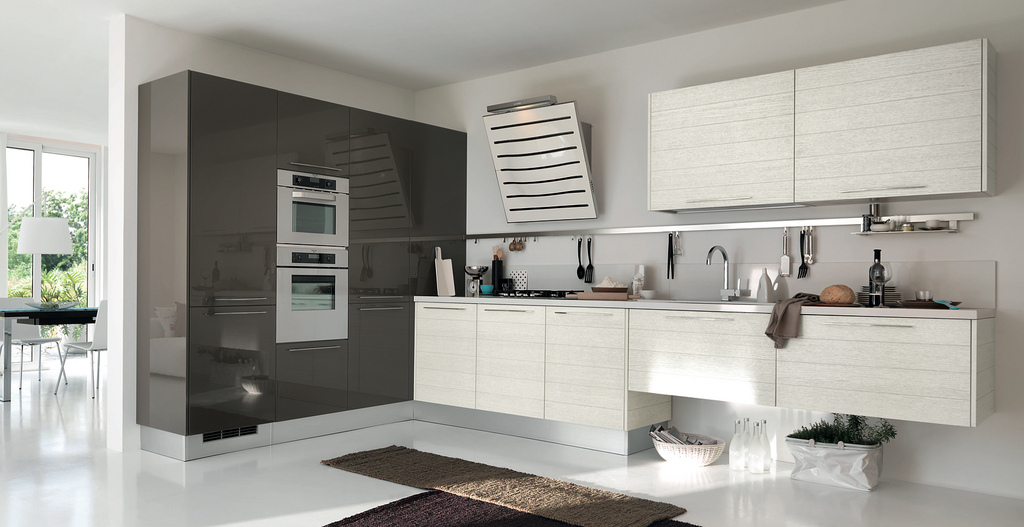 """This brown and white kitchen is nicely understated. Instead of additional shelves or cabinetry, the design is further simplified by attaching a single rack that lines the wall above the sink, and open """"storage"""" space underneath part of the counter area."""