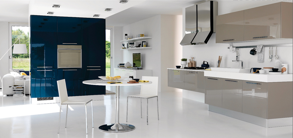 This beige and white kitchen is very open and connected to the rooms adjoining it. It only seems to be separated by the deep blue (a nice color choice) large cupboard area.