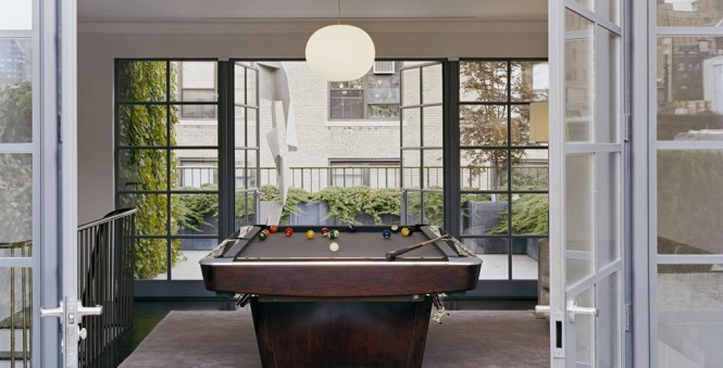 The pool table is placed vertically, leading to the entrance to the outdoor garden. It helps to define the space as one of entertainment, recreation, and relaxation.