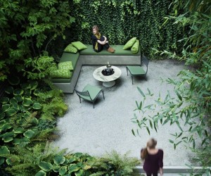Rees designs both interiors and landscapes and this small backyard of a townhouse overflowing with greenery is but one testament to their modern, simple yet stunning and functional style. They have maximized a small space by covering most of the walls with ivy, planting trees on the sides, and even adding green touches to the outdoor furniture. The result is a small backyard oasis of a townhouse in the city.