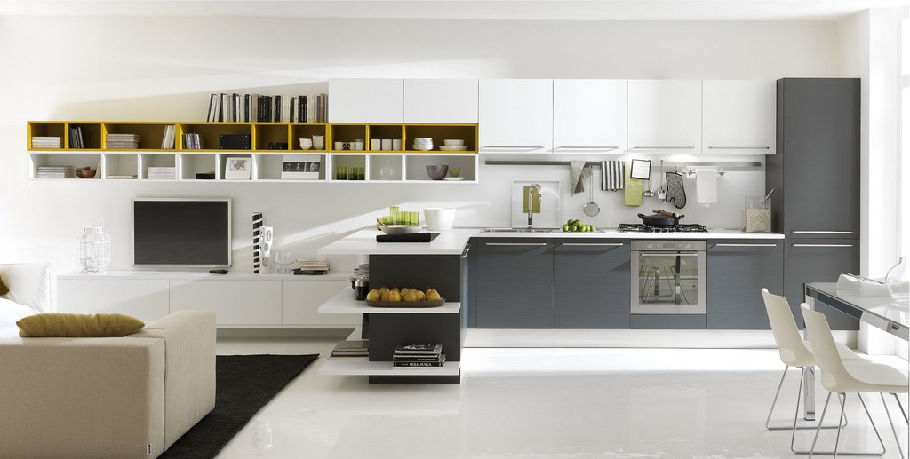 Ferriani likes to play subtley with color. Here, the kitchen is a simple grey and white that trails off into a yellow and white living area.