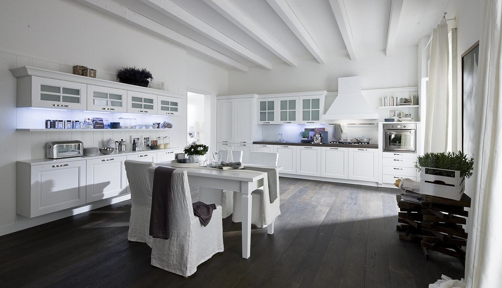 This design is perhaps my favorite out of the bunch, because I feel it melds the traditional, antique, rustic elements with the modern ones. The white cabinetry is reminiscent of a country farm, as is the dark wood flooring, yet the planks in the ceiling help to streamline the room and the simple furniture offers the modern vibe.
