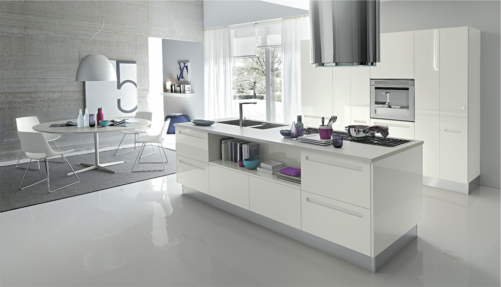 This kitchen is simply an island and cabinetry, mostly composed of white steel, but with touches of pretty purples and blues in the decor and kitchen utensils.