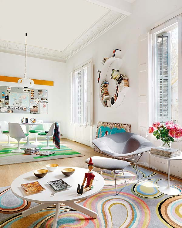 The swirling bookshelf and Pinocchio toy give the living room a playful vibe, while the french windows and flower arrangements make it refined and pretty. There is a meshing of colors and of styles (antique and modern) all in this one room.