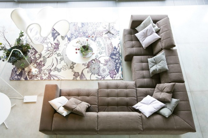 The beige couch looks quite versatile. Make it homey and sweet with a floral print rug, or eliminate the rug and substitute with dark pillows, and it will instantly become more modern and serious.