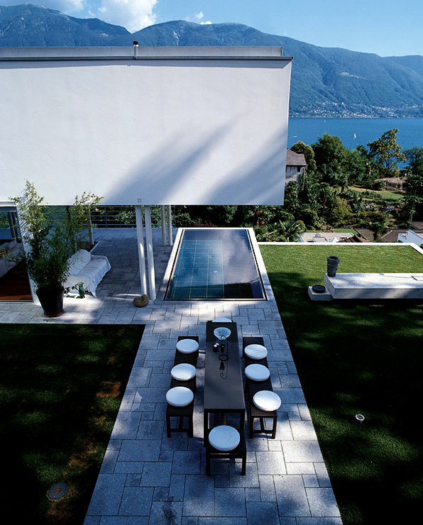 The east wing of the building extends as an overhang above dark granite tiled pool with shimmering water and a spectacular view of the Swiss Alps and deep blue waters of Lake Maggiore. The overhanging roof of the villa also protects it from strong sunlight.
