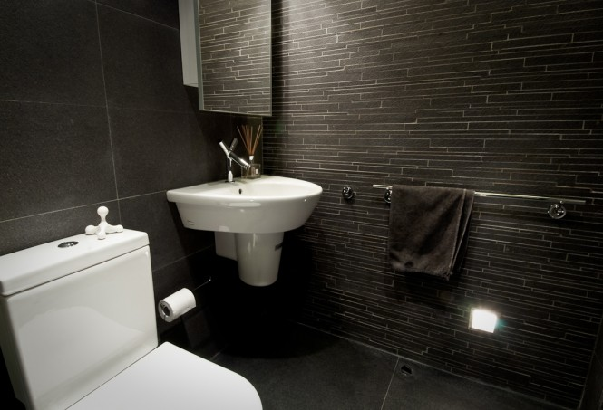 The bathroom is decorated in stark contrast to the warm wood, with cool anthracite floor, slate feature tiles, and grey veined marble walls.