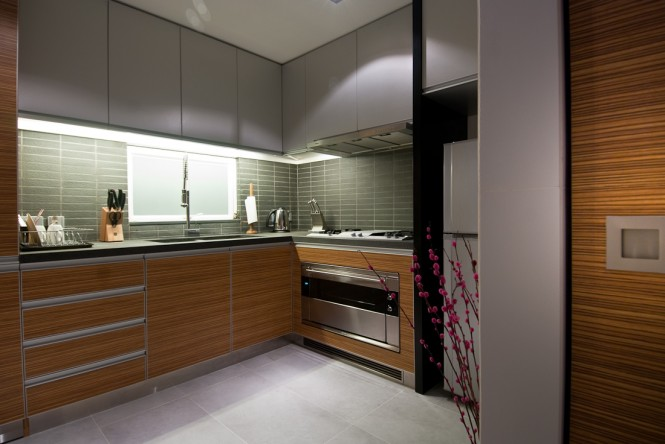 The kitchen sees a repetition of grey tiles and a paler floor that matches overhead cupboards, kept light to achieve an airier feeling in a heavily utilized space; however, the main body of the kitchen stays in-keeping with the wood tone seen throughout the rest of the home.