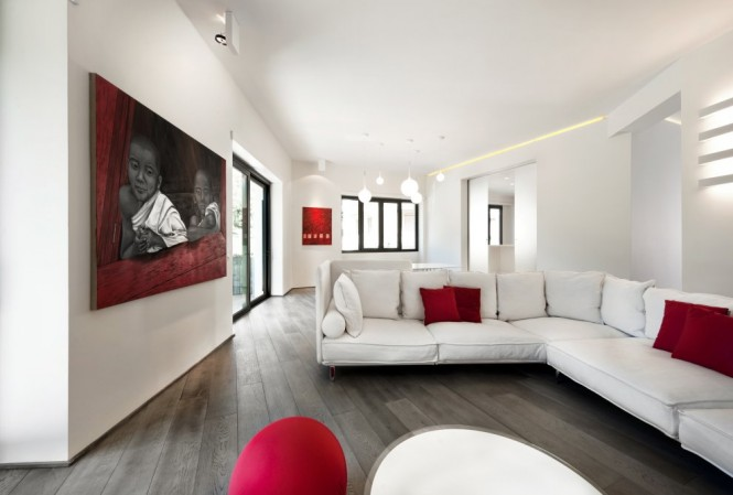 A continuous flow of living areas was created, with the large contemporary living room flowing into a modern dining area, and finally a minimalist kitchen that can be closed off with two sliding doors of white glass. With a seamlessness enabled by one cohesive color scheme, the minimalist interior achieves a relaxed feel within its highly styled decor.