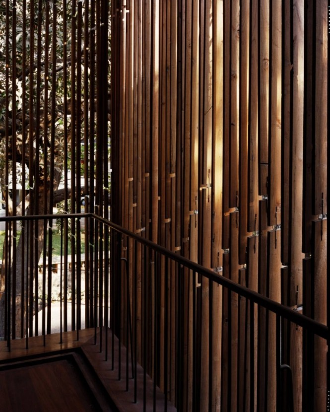 The internal décor pulls the outdoors inside by continuous use of bamboo wall treatments that play with light and shadow, and planted trellises that provide soft curtains of privacy and sectioning, evoking a feeling of natural protection from the busy urban environment beyond.