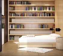 Fitted shelves flank the walls of several areas in the home, including the bedroom, where books appear to take precedence over anything else, including clothes and accessories; twin bedsides hold simple black reading lamps to illuminate all of that bedtime reading material.
