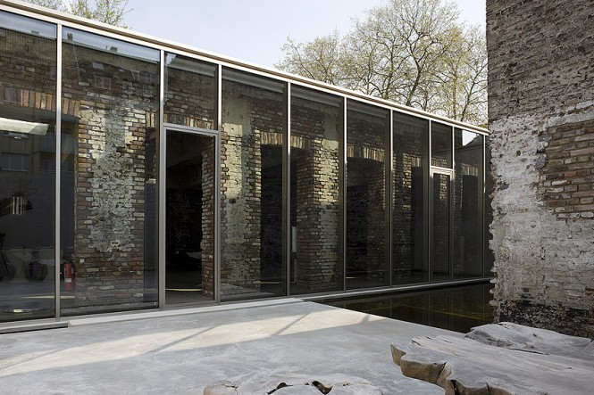The warehouse conversion sparked an interesting plan to allow light to penetrate into central living spaces from each side; to create dramatic effect and brighten the core, a shiny glass facade stands independently of the structure, contrasting with ancient walls and preserving the history.