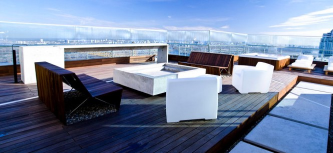 The top floor of the apartment is home to a huge rooftop terrace that enjoys panoramic views from a generous sun deck, a fire pit seating zone with handmade plank benches., or from a glass walled pavilion in more wintry weather.