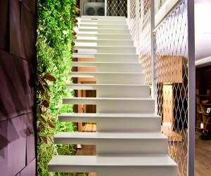 A green wall of plants grows vertically through the home, to bring the softness of nature into the manmade environment, running from the living-dining space down to the lower floor containing the lounge-home office space, plus the secondary living area that leads to the spacious master bedroom.