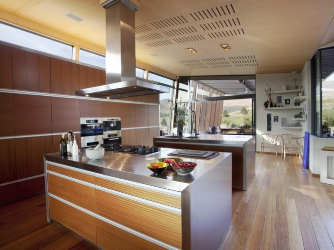 The kitchen has a double island feature that stands in front of a sprawling bank of storage units, big enough to house the paraphernalia of the entire home, if not just the culinary clutter.