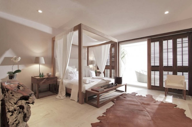 A romantic bedroom scheme greets you with a fairytale of a four-poster bed, complete with soft flowing drapes and fresh white bed linen. A cowhide rug spans the floor space to create a little warmth underfoot, amidst the cool marble floor.