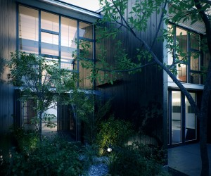 At the front of the home, a towering glass faade overlooks a zen-like courtyard, on the approach to a minimalist entranceway flanked in wood. Slender trees soften the lines of the modernistic architecture and encourage a more naturalistic feel that in turn leads into the pure materials of the interior.