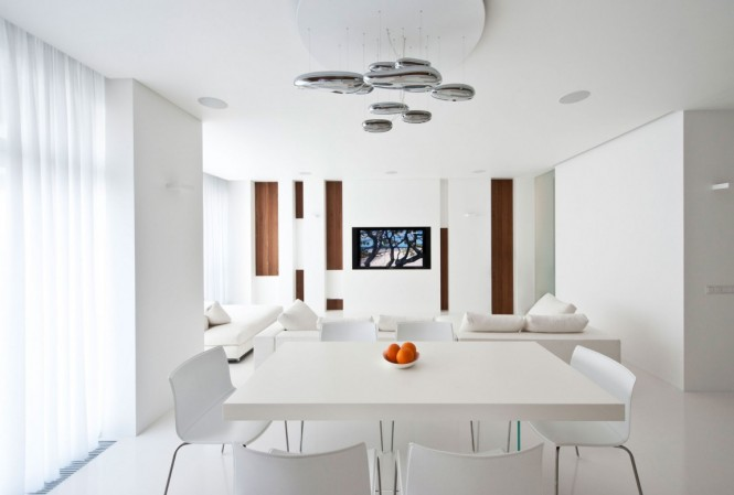 To continue the laid back luxurious style from floor to ceiling, the over dining table pendant light fixture is futuristic yet understated, visually interesting but not demanding of attention or causing distraction. The dining table itself blends in simply with its surroundings in a white on white setup.