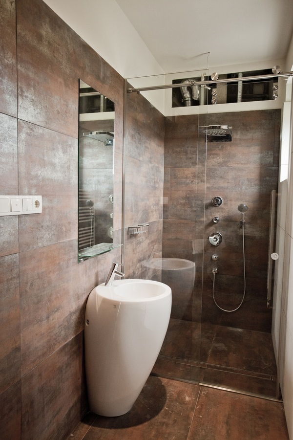 A shower area is decorated in decadent bronze tiles that compliment the ruddy hue of the floorboards. The overall look is lightened by the clean simplicity of modern white sanitary ware.