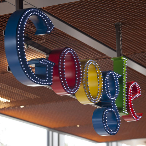 Dozens of miniature lights illuminate the outline of the colorful Google logo over the reception area.