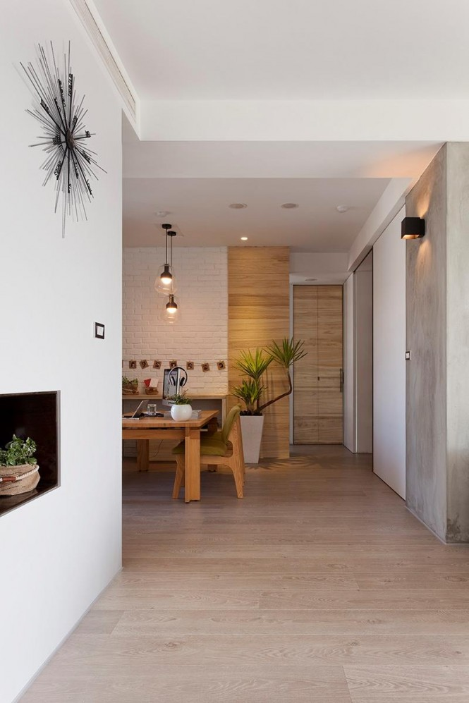 Wood cladding has also been taken up and over the walls to bring more warmth into the minimally decorated apartment, and much of the furniture employs a complimentary grain.