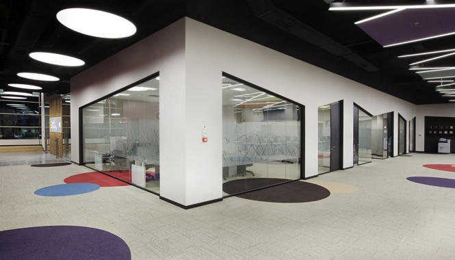 Beneath a chaotic and colorful designed ceiling, a circle carpet pattern decorates the floor, which is a familiar sight from other branch offices where it is used to reflect the company's corporate identity.