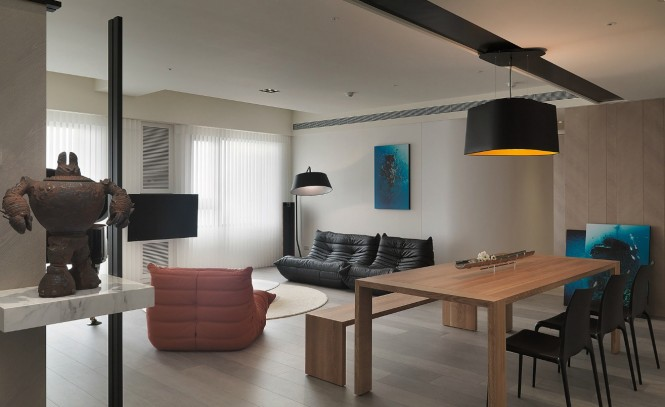 Bold orange accents are scattered throughout the open plan apartment, where a low slung accent chair sings in the zesty hue, and a large over dining table pendant shade reveals a matching lining.