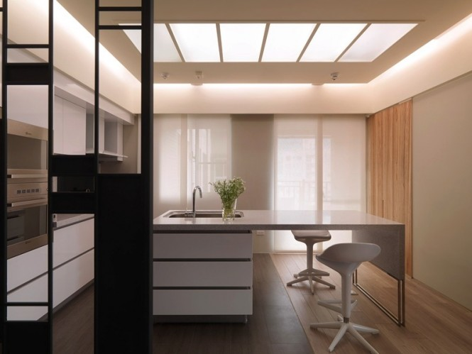 On the other side of the room divider, a slick kitchen also echoes the rectangular design in the simplicity of its handleless drawers and units, and a multi-sectioned skylight.