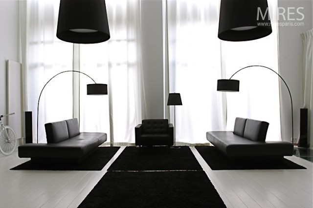 A symmetrical furniture layout creates a mirrored effect in the lounge area, complete with matching minimalistic sofas and slick black arc lamps to illuminate each side equally. This symphony of silhouettes stretches out across the white floor where a base of black throw rugs are perfectly aligned like a bridge over to, and beneath, the seating, and continues all the way up to the ceiling in the matching ebony pendant light shades.