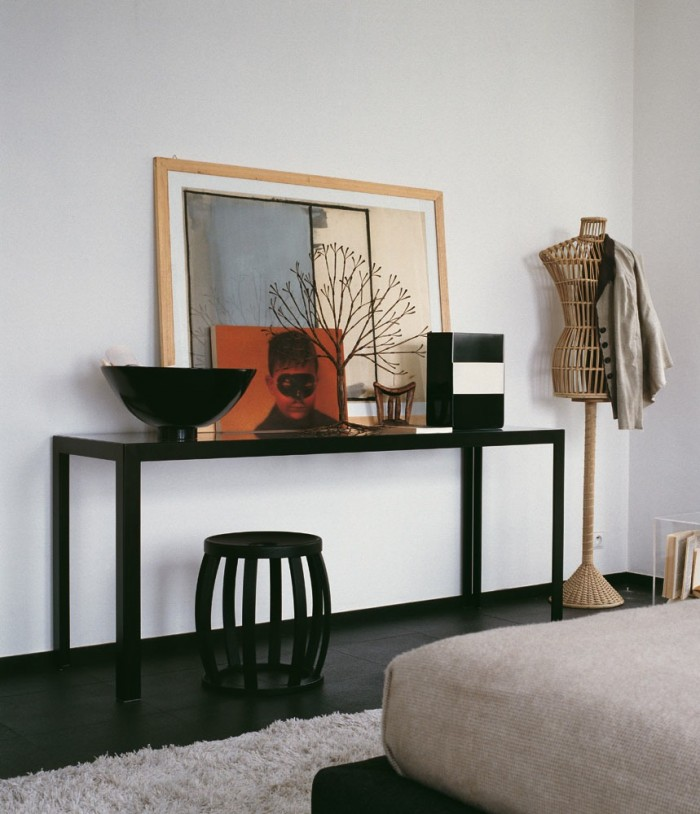 A console table is dressed informally with propped artwork and clean shaped bowl and vase.