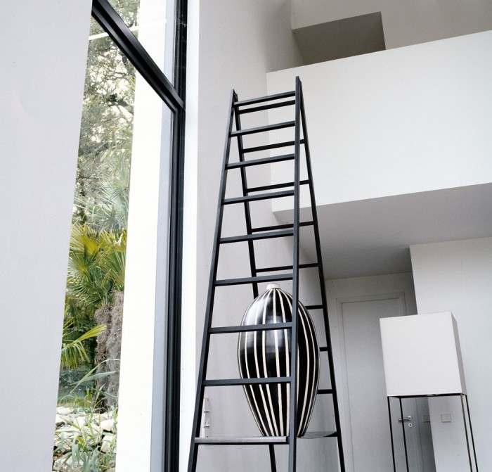 A monochrome vase sits precariously in the A-frame of a black ladder, drawing the eye up to the room's mezzanine level.