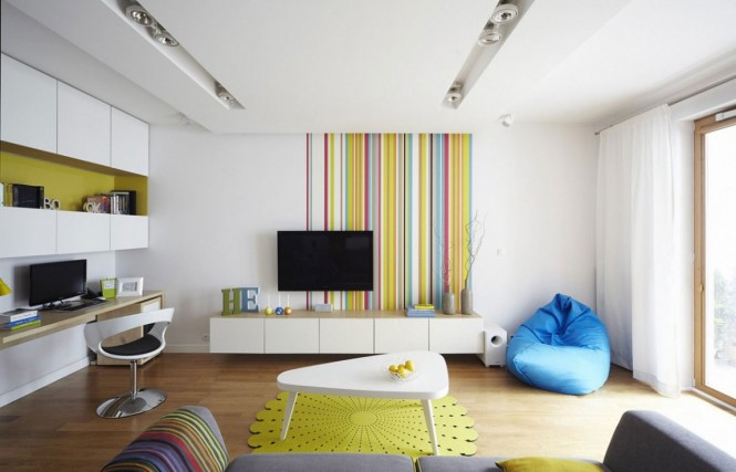 This home utilizes quirky wall treatments to really create a buzz, such as the dominant stripes of the lounge wall, and the typographical wallpaperspecially designed for this homethat backs the kitchen.