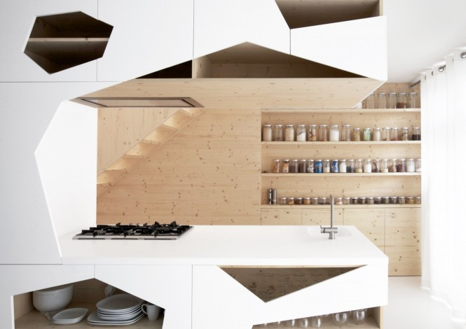Via i29Clever cutaways create irregular windows into the storage spaces of this kitchen, along with a series of recesses dedicated to an army of glass jars that are filled with dried cooking ingredients that not only keep culinary delights within easy reach, but brings color and texture to an otherwise neutral design.