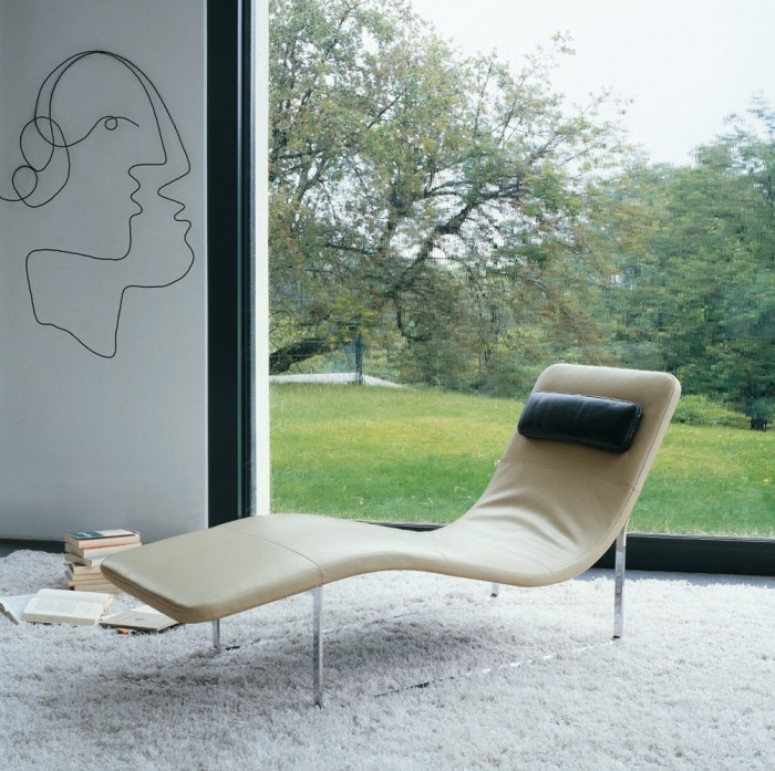 A simple line drawing adorns the wall of the relaxation area equipped with a modern sweeping chaise lounge.