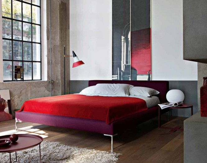 In the bedroom, a clash of purple bedstead and red bedcovers create a passionate palette to warm the cold concrete walls.