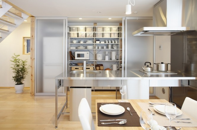 A stainless steel kitchen island looks out over the dining area, providing an ideal setting for entertaining and family gatherings.