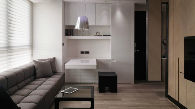 Adjacent to the sofa stands a bespoke set of storage units, colored white and kept handleless so as to blend in with the wall. This bank of units offers concealed storage, a display shelf for much loved items, and a suspended worktop that could be used for both study or dining purposes.