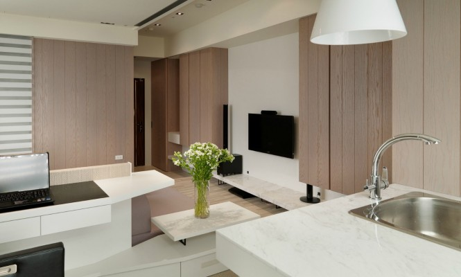 The white marble countertops, used in various forms in the design, both reflect the light and create a look of quality.