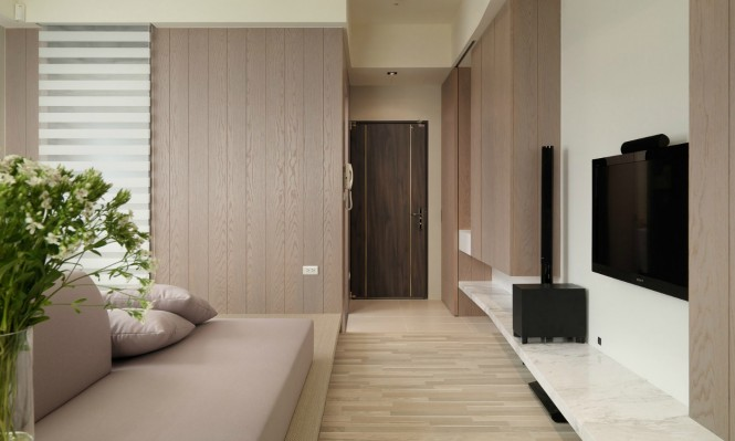 A wall of wood cladding matches the finish of the wooden cabinetry to achieve continuity of materials and color.